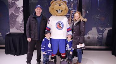 Family posing with mascot Slapshot
