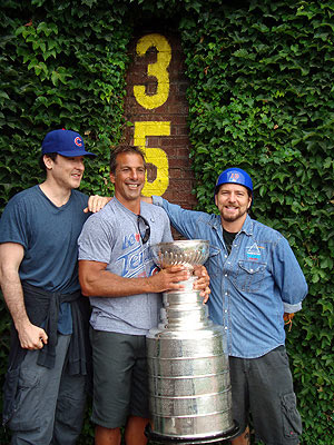 John Cusack, Chris Chelios and Eddie Vedder tour the ivy covered and unforgiving outfield wall of Wrigley Field
