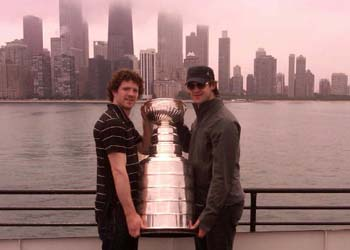 Colin Fraser and Brent Seabrook pose with the Stanley Cup during a lunch hour boat cruise.