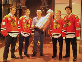 Jonathan Toews, Duncan Keith, Jay Leno, Patrick Kane and Brent Seabrook posing for a photo with the Stanely Cup.