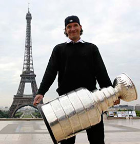 Cristobal Huet and the Stanley Cup posing for a picture in front of the Eiffel Tower in Paris