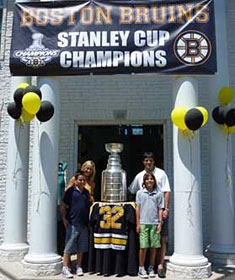Don Sweeney and family sharing a moment with the Stanley Cup outside the home of friends