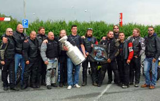 Tomas Kaberle and the Stanley Cup posing for a photo with some motorcycle enthusiasts.