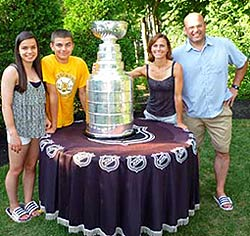 Peter Chiarelli and his family sharing a moment with the Stanley Cup at their home in Lexington, MA.