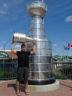 Johnny Boychuk and the Stanley Cup posing for a photo beside a giant replica Stanley Cup in Edmonton, AB.