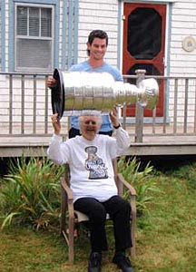 Adam McQuaid helping his grandmother hoist the Stanley Cup during a visit at her home in Cornwall, PEI.