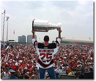 Joe Nieuwendyk raises the Stanley Cup at a rally.