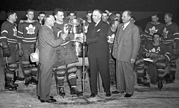 Manager Conn Smythe Captain Ted Kennedy Receive The Stanley Cup From NHL President Clarence Campbell With Coach Hap Day Flanked By Team After Game 4 Of