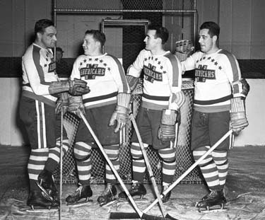 Charlie Conacher, Busher Jackson, and two New York American teammates gather around the net.