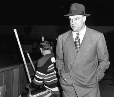Charlie Conacher behind the bench of the Chicago Black Hawks.