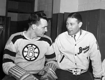 Boston Bruins head coach Dit Clapper talks to one of his players.