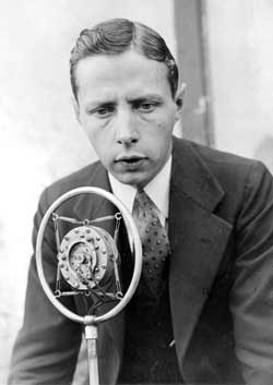A young Foster Hewitt poses in front of a microphone