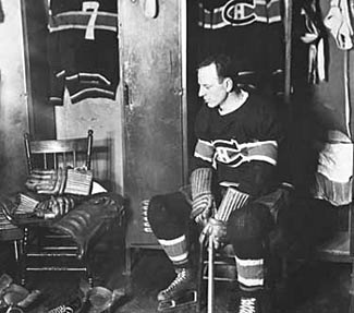 Aurele Joliat sits beside the empty seat where his good friend and teammate Howie Morenz used to sit before his passing on March 8, 1937.
