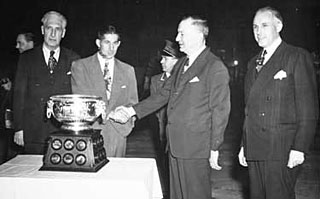Lester Patrick (left) and Clarence Campbell (right) are on hand as Elmer Lach receives the trophy named after Art Ross (2nd from right) in 1948.