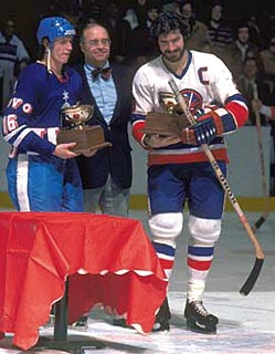 Bill Torrey makes a presentation to Islanders captain Clark Gillies and a member of Telsa Pardubice following an exhibition game on January 4, 1978.