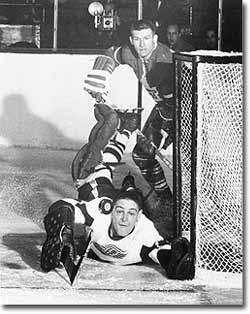 Sawchuk stretches to push the puck away