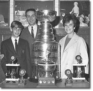 Terry Sawchuk with his wife Pat, son Jerry and a few of his awards